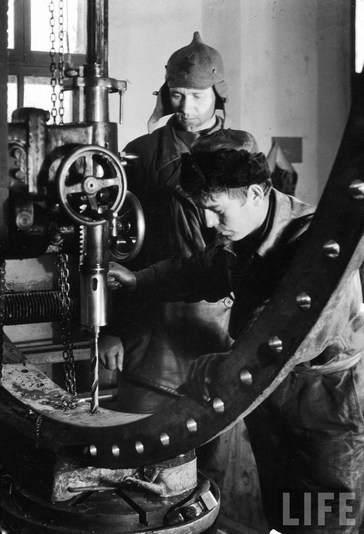 Two Russian Workers Running A Drill Press In A Machine