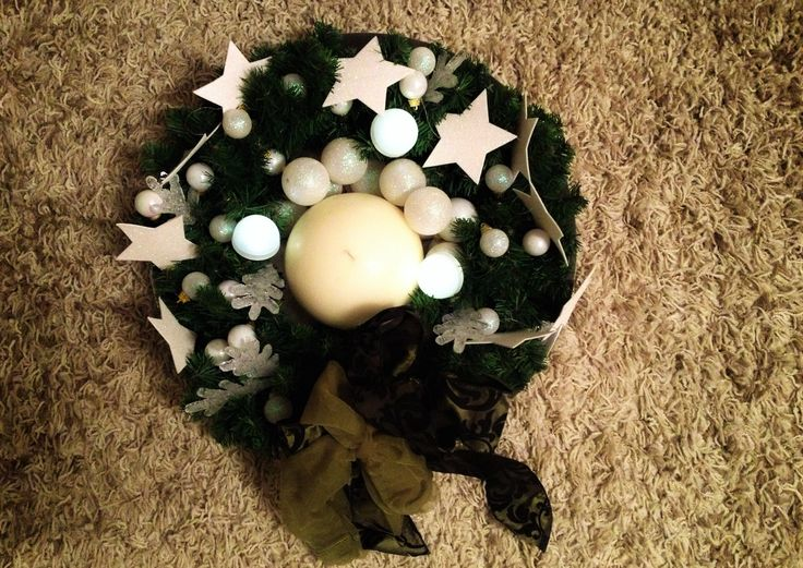 Iced wreath_with white stars_snowflakes_Christmas balls_candle and bow