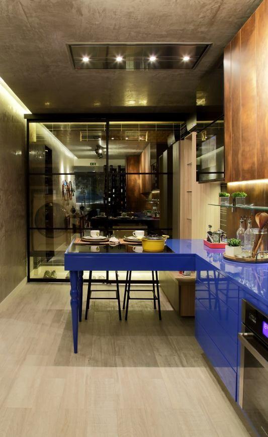 Cozinha com Área de Serviço e Varanda Gourmet. O ambiente de 43m² é paginado com porcelanato que lembra madeira e recebe armários suspensos com diferentes alturas. Na parede e no teto foi aplicada a textura stucco veneziano, de efeito marmorizado. Com essa base, os elementos de destaque passaram a ser a bancada e os armários laqueados no tom azul real. Portas de correr em vidro Reflecta separam o ambiente da área de serviço e recebem uma TV embutida.