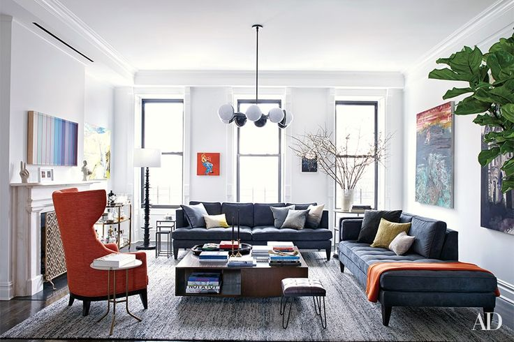 A Jonathan Adler light fixture crowns the living room, where Room & Board sofas are grouped with a high-back chair designed by Powell & Bonnell for Dennis Miller Assoc., Arteriors nesting tables, and a bespoke Trace Lehnhoff cocktail table; the blanket is by Hermès. An artwork by Brian Wills is mounted over the mantel, the small orange painting between the windows is by Noah Davis, and the seascape on the wall at right is by Annie Lapin; the rug is by ABC Carpet & Home.