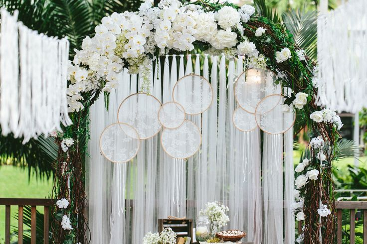 Ethereal white floral wedding arch with lace dream catchers and tassels! More…