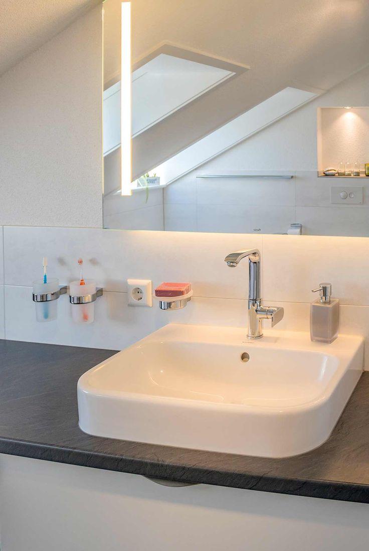 Heller Waschbereich, auf dunkler Tischplatte steht ein weißes viereckiges Waschbecken mit abgerundetetn Ecken, Viereckiger, schlichter beleuchteter Spiegel