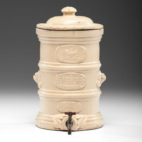 English Stoneware Water Cooler English, 19th-20th century. A stoneware cooler with removable plate filter and metal spout, having a banded body with lio