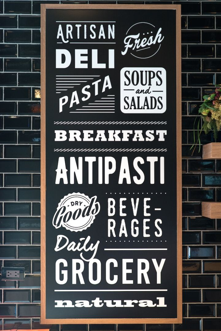 A black and white color palette combined with wooden fixtures becomes a neutral background for the specialty products and ingredients to shine. Vintage hand-painted graphics on black wall tiles add to the welcoming atmosphere of this neighborhood grocery store.