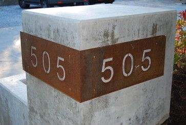 I like this!  Imagine the block made or faced with stone (charcoals and sienna).  Have the house numbers cut out of Corten like this, but standing a few inches away from the stone and lit from underneath but behind the corten to illuminate the numbers at night.  There is a mailbox built into the block, facing the street.