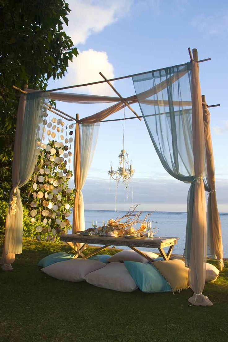 Gorgeous outdoor picnic under a bamboo DIY canopy draped in muslin gauzy sheers with chandelier suspended, and driftwood centrepiece. Mounded cushions for seating, she'll curtain and ocean view a la carte dining entertaining  Cute for a wedding ceremony DIY gazebo altar frame