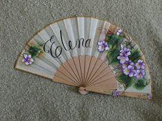 Abanico pericon de madera, pintado por la parte delantera. Un delicado abanico personalizado entre la sutileza de las violetas. medida: 23 c...