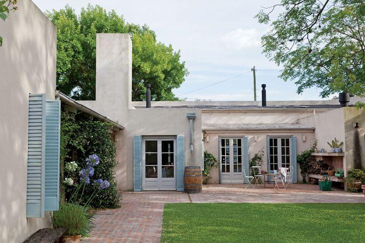 Jardín de una casa remodelada con canaletas en el techo que se unen en un conducto central para llevar el agua de lluvia a un barril de madera.