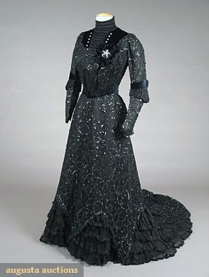 "RUSSIAN LABEL BLACK TEA GOWN, c. 1905 - 2-piece sequin decorated heavy cotton lace over silk satin, black chiffon flounces, velvet ribbon trim & diamante brooch on wired black velvet cockade, label stamped in gold on black petersham, ""Mody i Platji S Peterburg Fontanka u Chernyshevamosta"" Translation: ""Fontanka Fashions & Dresses St. Petersburg at the Chernysheva bridge"", black silk taffeta linings, long skirt train, Sh-Sh 13"", B 38"", W 24"", Skirt L 39""-60"", (minor sequin loss) excellent."