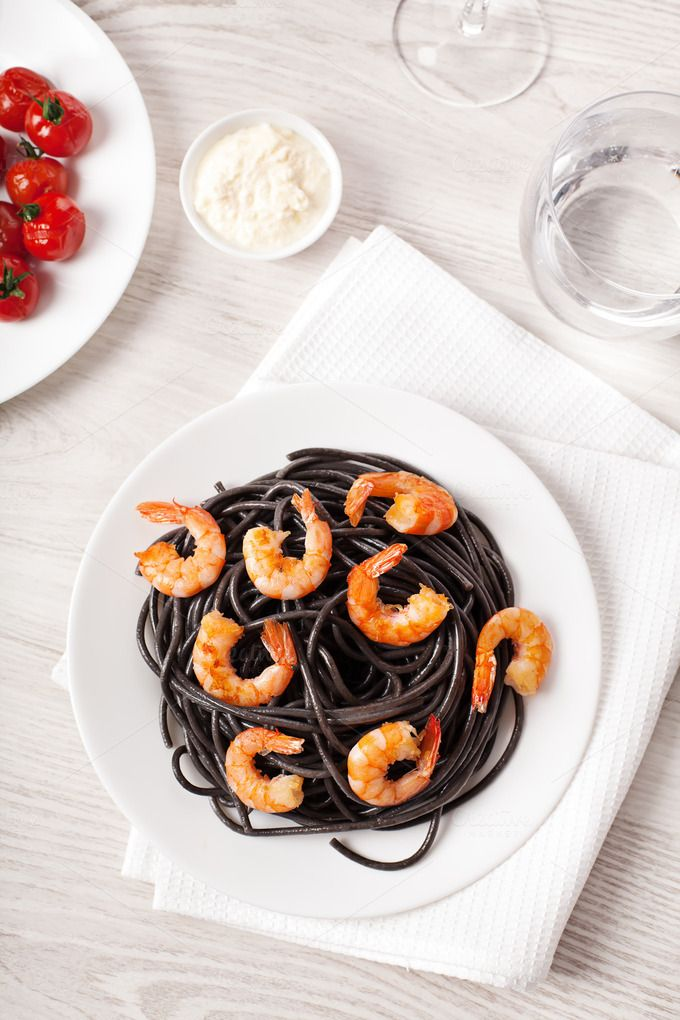 Black italian pasta with shrimps food on light background by Olha Klein on Creative Market