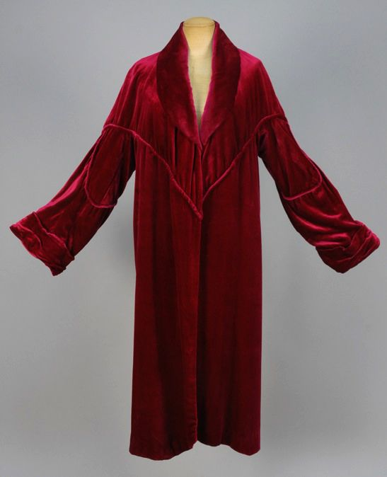 LUCIEN LELONG VELVET EVENING COAT, 1920s Garnet silk with shawl collar and self piped yoke and sleeve details, ruched cuff. Labeled. (Alterations, re-lined, collar edge torn, seam separation)