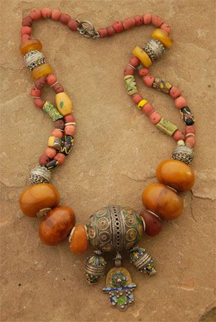 "by Nan Stine | The Hand of Fatima and two barrels dangle from the large Berber ""egg"" that is the focal point of this piece. Large copal amber beads, Venetian trade beads, smaller Berber and amber beads and coral-colored glass complete the strand.  {Price not published, please contact seller}"