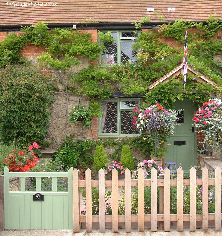 English Country Garden: Pottery Cottage in Oxfordshire. The tiny front garden with hanging baskets and tubs of flowers.