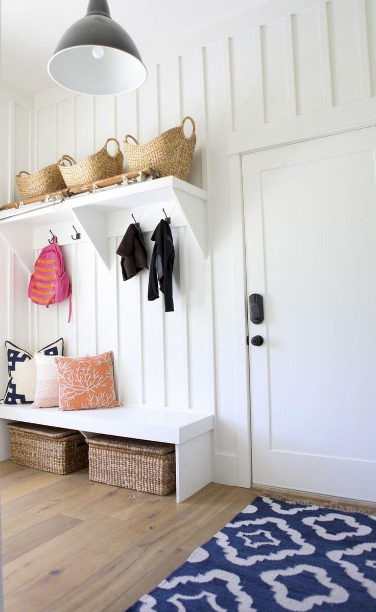 petite entrée blanche et moderne aménagée avec des étagères murales et un petit banc avec paniers tressés