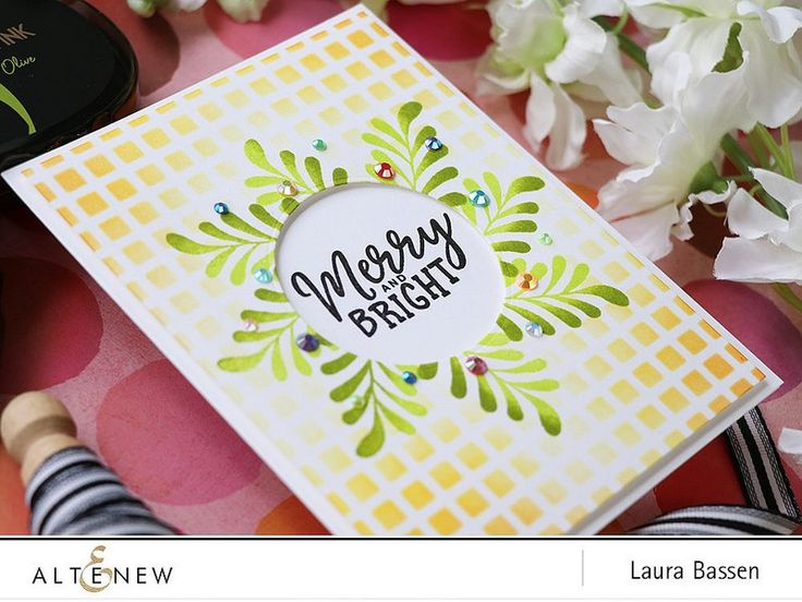 Hi there! Laura here and today I have a festive project to share featuring a few of the holiday themed products from Altenew. To begin I stamped the smaller mistletoe image from the Majestic Mistletoe stamp set repeatedly to create a wreath-like shape using Bamboo & Olive ink. Then I die cut a circular window …