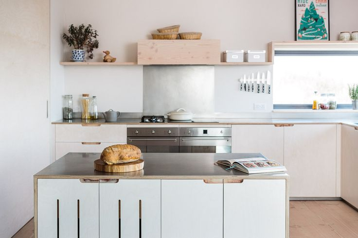 Brushed stainless steel worktops and splashbacks in a contemporary kitchen. The brushed steel sheet is bonded with the plywood. Dinesen Douglas Fir flooring offcuts are used to create the floating shelving and the extractor box.