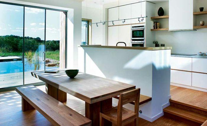 offene küche mit theke holzboden treppen esstisch holz sitzbank holz holzstuhl weiße küchenfronten schwimmbadaussicht