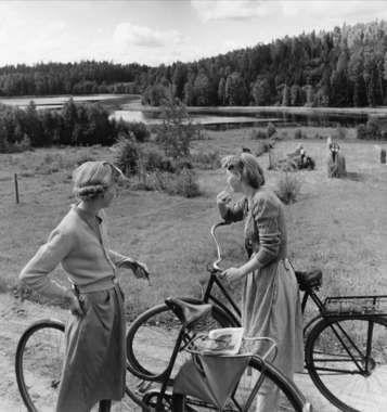 Två flickor med cyklar på landsväg