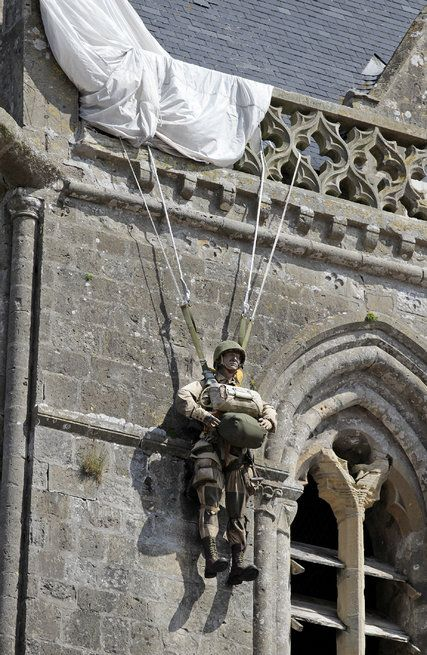 The French town of Sainte-Mere-Englise Is a Living D-Day Memorial. It was the first village in Normandy to be liberated by the Americans.  An effigy of Private John M Steele who landed on the church tower.on D-Day, 6th June 1944. He was made famous in the film, The Longest Day