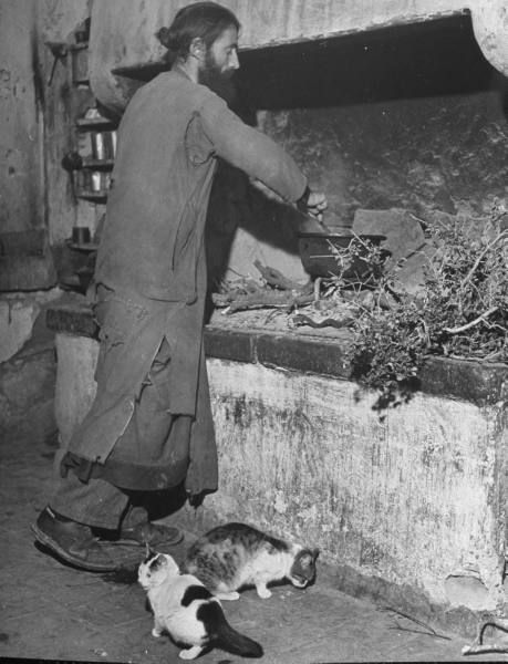 Civil War/Greece. An Orthodox priest cooking in the monestary kitchen. Location:Louzesti, Greece  Date taken: December 1947  Photographer: John Phillips