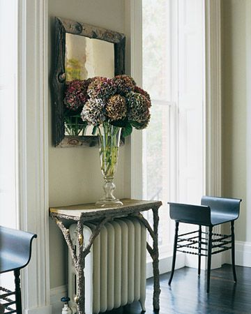 Table--In the living room of the West Village town house, under an antique French concrete faux-bois mirror frame, a faux-bois table made by Stephen straddles a vintage radiator.