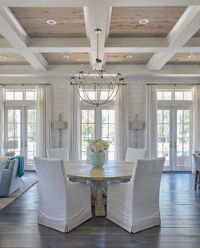 The dining room boasts a glossy white coffered ceiling accented with pecky cypress coffers accented with an iron chandelier. The round salvaged wood dining table surrounded by white slipcovered dining chairs. Lighting is Lowcountry Originals Spring Island Basket.