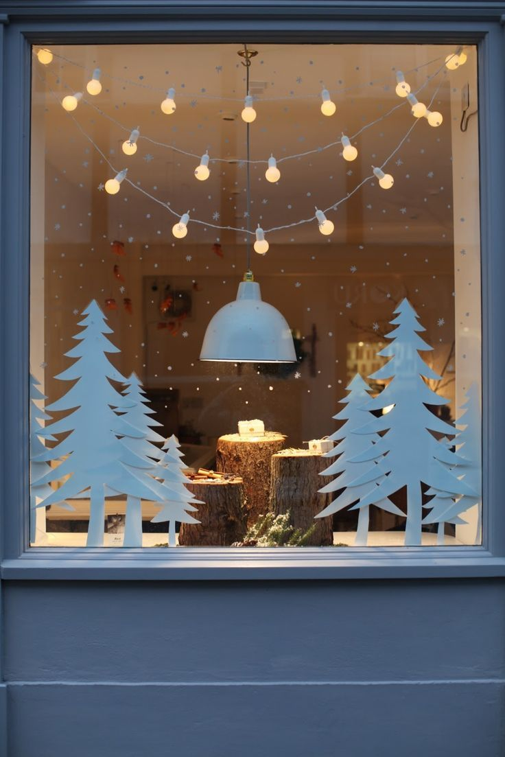Festive shop window display that would work really well in a home too – simple white silhouette fir trees and snowflakes