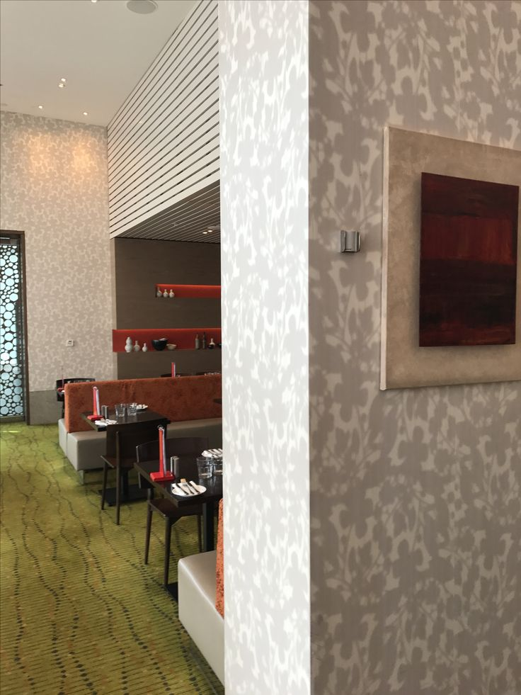 Photo 10: This restaurant at Crown has used a neutral coloured floral print wallpaper to decorate. The floral pattern adds detail but by using neutral tones it doesn't over power the other elements in this space.