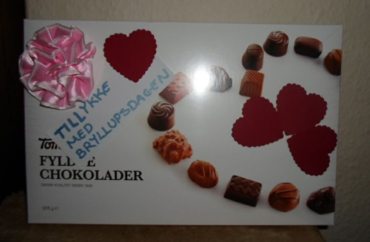 A box of chocolate decorated with hearts, a sign and a flower. A present for my parents on their weddingday.
