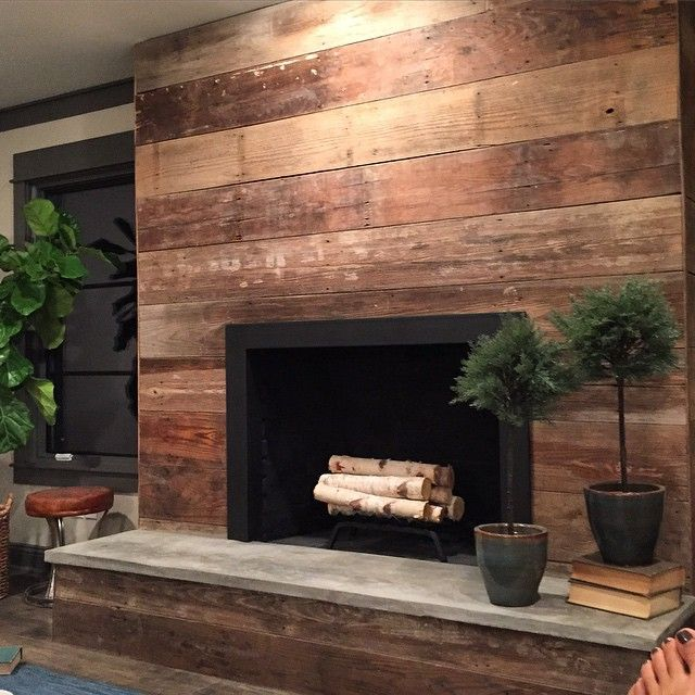 The space, now merged with the main living room, now has an updated fireplace with a surround clad in reclaimed wood and concrete hearth. Fixer upper