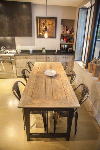 Dans la partie coin repas de la cuisine, sol en béton ciré remplaçant les tomettes existantes, table sur mesure et chaises métalliques d'usine (modèle Multipl's, création Joseph Mathieu, vers 1922).