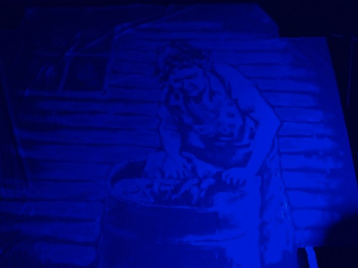 Washerwoman. In detergent on bed sheet. Illuminated by UV light.