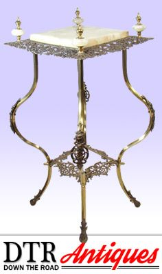 This beautiful cast iron and brass plant or lamp stand has four onyx finials with brass tops and an ornate reticulated top and bottom shelf on square brass legs with applied iron filigree mounts on knees and feet. $495