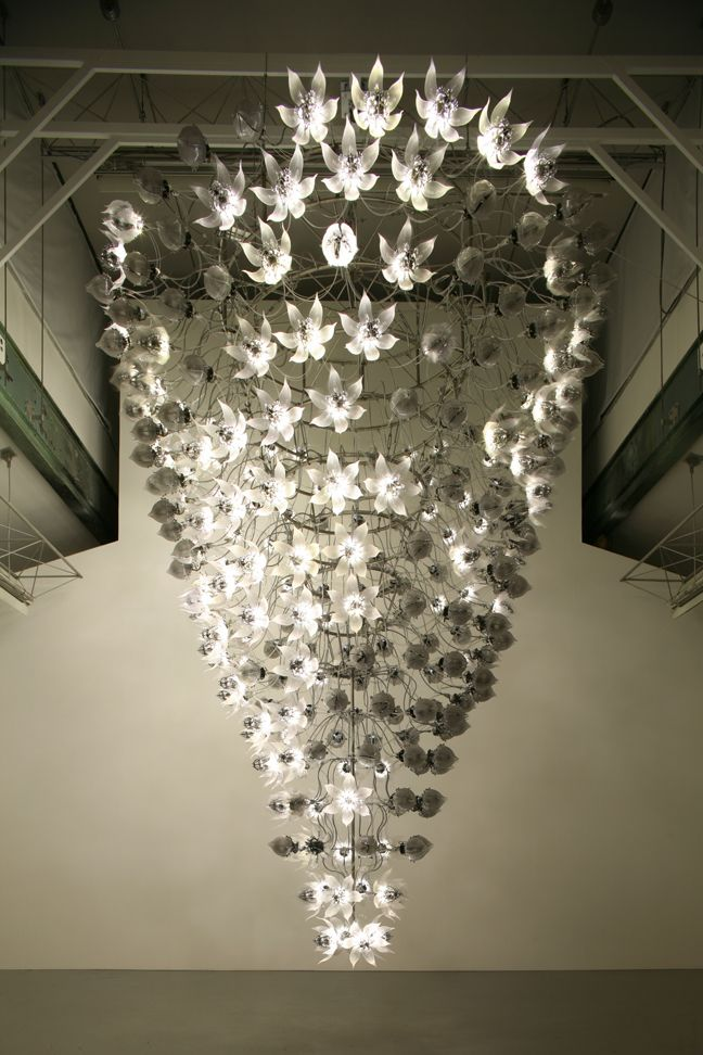Una Lumino, is a kinetic sculpture by Korean artist Choe U-Ram.  Standing at just over 17 feet tall, the whirlwind of elegant robotic flowers are automated to bloom open, shining a brilliant light, and revert back to their closed state.