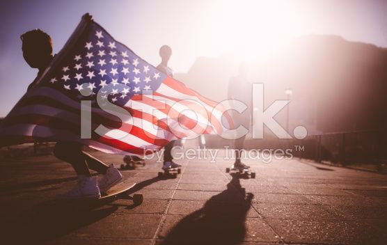 African American longboarder flying an American flag royalty-free stock photo