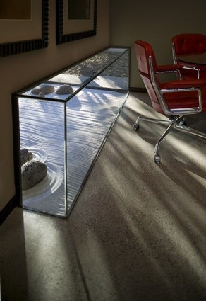 An inset glass box is used here to capture the reflected light of an outdoor Zen garden and to bring it indoors along the floor. The wall becomes a glowing prism of light during the day, and a glowing alcove as seen from the outside at night. Simply beautiful.