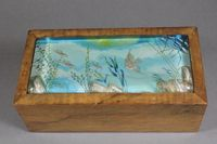 "Ben Shillingford for Dunhill, a walnut aquarium cigar box, the hinged top inset a lucite panel depicting flying and angel fish  amongst a sub-aquatic setting, 3""h x 8.5""w x 4.25""d  SOLD FOR £1000"