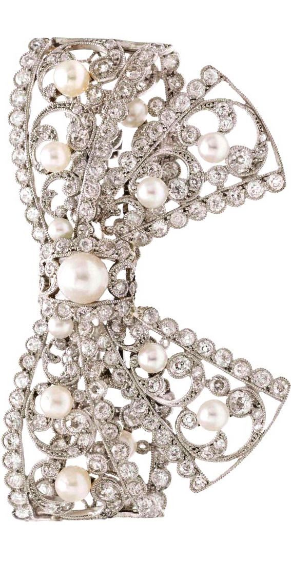An Edwardian Platinum, Diamond and Pearl Bow Brooch, in an openwork design with millegrain details, containing numerous old mine and old European cut diamonds weighing approximately 4.75 carats total, one pearl measuring 6.75 mm in diameter, four pearls measuring approximately 4.25-4.75 mm in diameter and six pearls measuring approximately 3.37-4.14 mm in diameter.