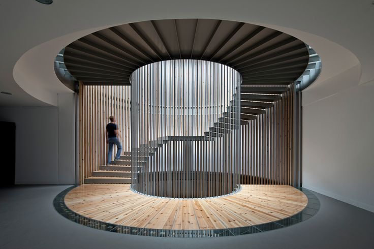 A very unique styled stair case ! Love the way each column is placed to draw your attention in a circular motion towards the top of the stair case .