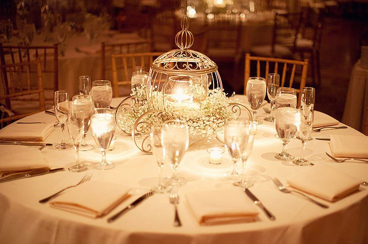 Cinderella's carriage doubles as a candleholder in this glowing centerpiece. Image Source: Jonathan Ivory P...
