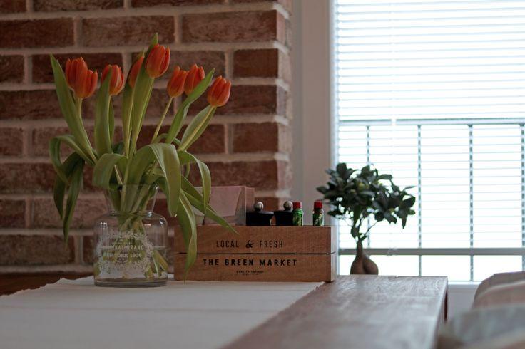Kvety rezané aj v kvetináčoch zabezpečia zútulnenie priestoru. V pozadí tehlová stena, ktorá bola uložená vlastnoručne majiteľmi.