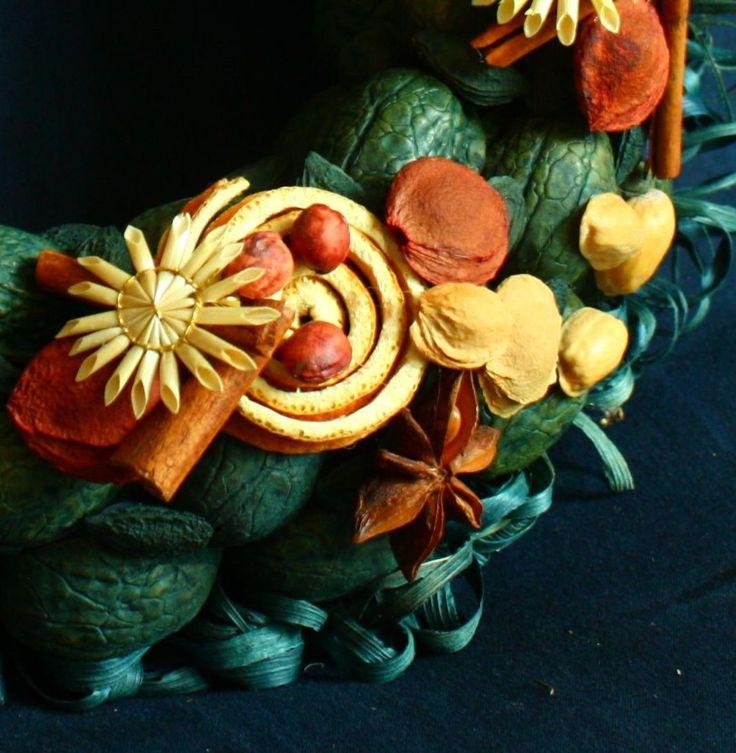 Vítací věnec 1 Ozdobný věnec z tónovaných přírodních materiálů. Je vyroben ze skořápek oříšků, pecek, trávy, slámy, sušených pomerančů, pomerančové kůry, šustí, koření. Upevněn je na pevném slaměném korpusu. Korpus je obalen batikovým papírem. Ze zadní strany je poutko na zavěšení. Na dveře se dá pověsit za delší pruh lýka, nebo stuhu. Průměr cca 28 ...