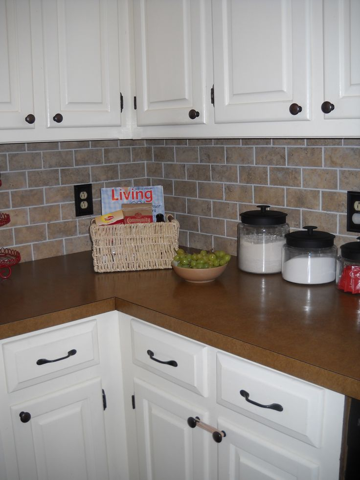 "Our DIY brick backsplash using vinyl floor tiles cut into mini ""bricks"". Total cost under $20:)"