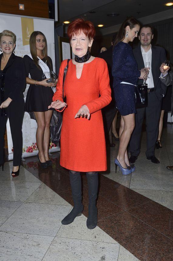 Brylująca i straszna Maria Czubaszek. Płomienna czapka, podejrzana obroża i krwista kreacja przywodzą na myśl `Sok z żuka`…W tle salonowy taniec godowy. Urzekające.  Więcej na Moda Cafe!