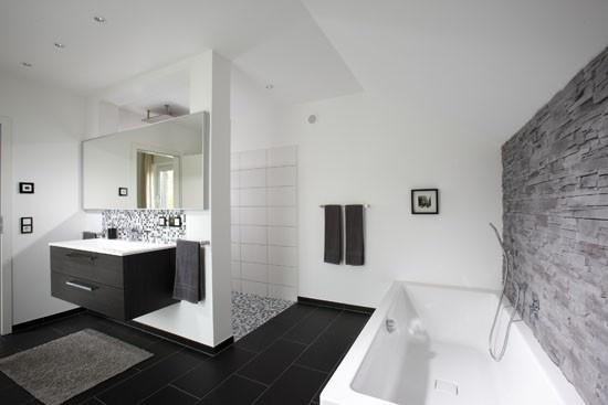 Fertighaus Wohnidee Badezimmer mit Badewanne und Natursteinwand