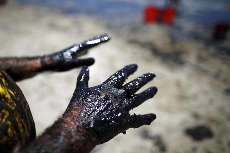 Volunteer William McConnaughey, 56, who drove from San Diego to help shovel oil off the beach, stretches out his hands after carrying buckets of oil from an oil slick along the coast of Refugio State Beach in Goleta, California, May 20, 2015. REUTERS/Lucy Nicholson