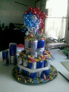 Ultimate birthday cake. 10 packs of red bull stacked, 3 family sized bagsof jolly ranchers. on a pizza pan, and held together by silver duck tape strips folded in half.with a red, white and blue bow!