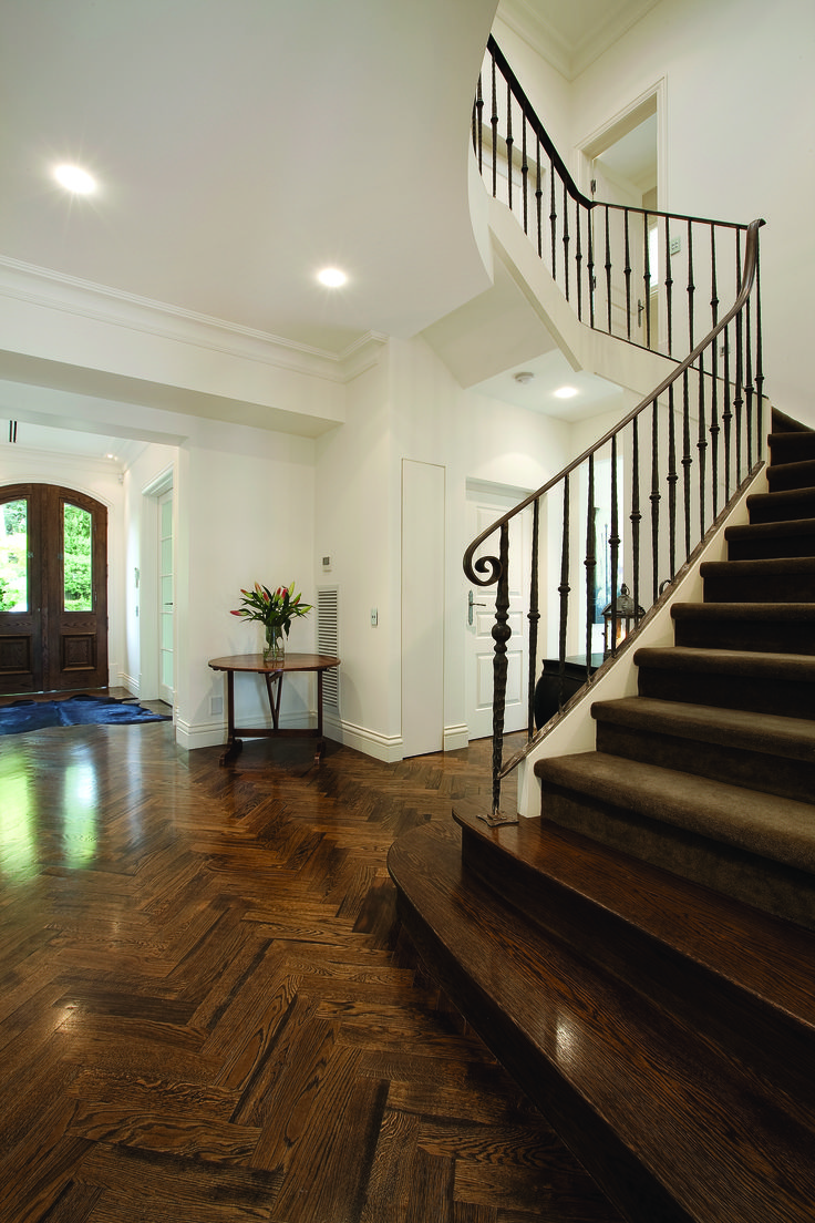 Curved Staircase With Timber Handrail, Wrought Iron Baluster, Timer and Carpet Finish. Ravida- Property With Distinction