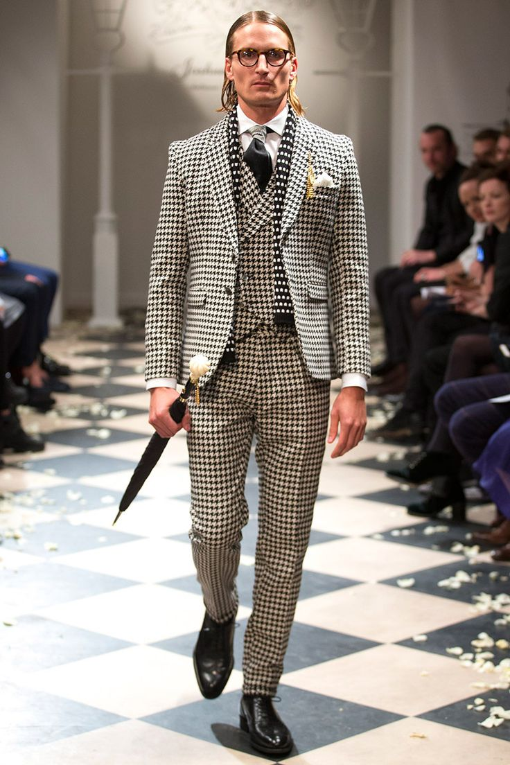 [Joshua Kane]: traditional menswear elements — three-piece suits, double-breasted vests, houndstooth, umbrellas, pocket watches