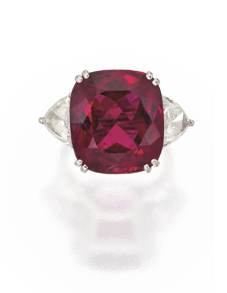 PLATINUM, RUBELLITE AND DIAMOND RING, CARTIER. Centered by a cushion-cut rubellite weighing approximately 19.60 carats, flanked by two triangle-shaped brilliant-cut diamonds weighing approximately 4.00 carats, size 5½, unsigned. With signed box.